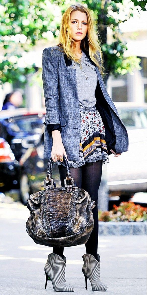 Blake Lively wears a gray t-shirt, printed miniskirt, blazer, tights, ankle booties, and a satchel