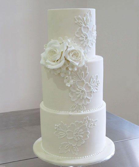 White Lace. This tall beauty features white piped lacework on white icing. Stunningly understated and finished with a posy of hand made sugar roses.
