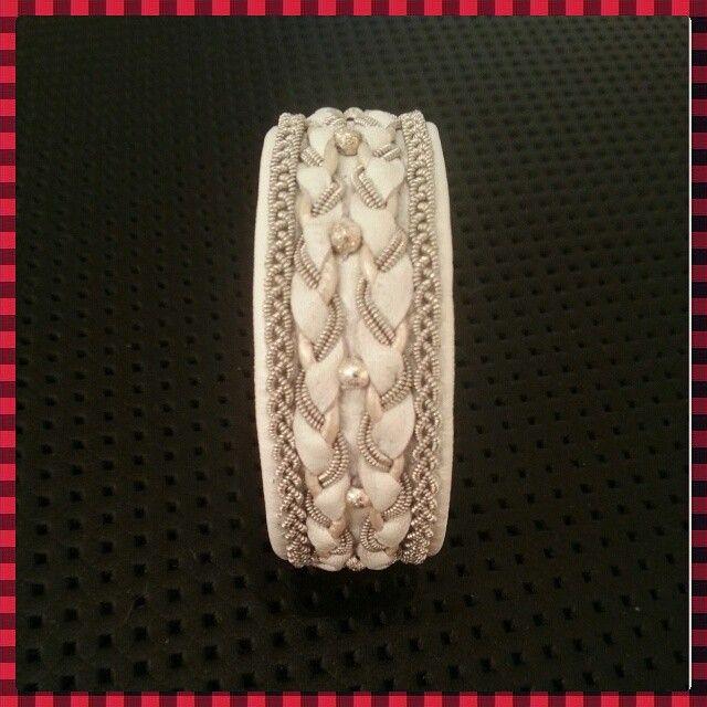 Ett vitt tenntrådsarmband som jag gjort med vitt renskinn, skinn rundrem, tenntråd (4% silver) och frostade äkta silverpärlor. En tenn stavs knapp.