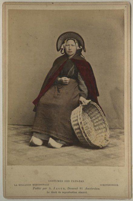 Vrouw in Scheveningse dracht; negotiante (visverkoopster) met vishoed en vismand; zij draagt een katoenen gebloemd jak, een donkergekleurde katoenen rok, een heel smal doekje, een schoudermantel met waarschijnlijk rode baai gevoerd, muts met klappen, ijzer met stukken, haar in een toer. ca 1890 A. Jager, Amsterdam #ZuidHolland #Scheveningen