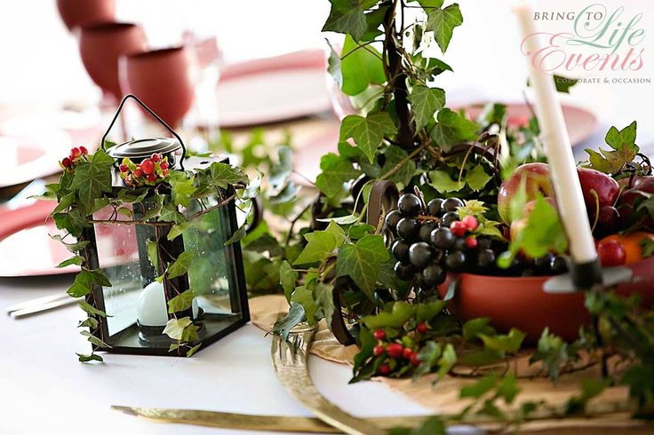Medieval setup with lantern, fruit, scroll, candles and flowers