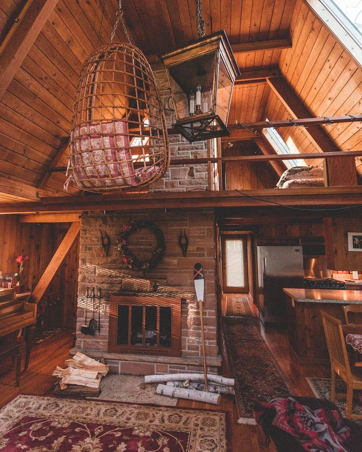 @kylefinndempsey standing in the living room of an Indiana A frame. That hanging chair was able to be lowered from a pulley in the loft, which ended up giving you the perfect seat in front of the grand fire place. Location: Fox Lake, Indiana