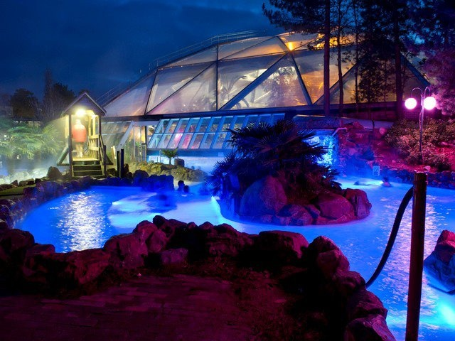 The outdoor pool at night by Center Parcs UK