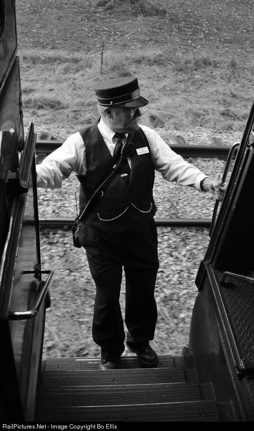 The passenger conductor of TVRM's Bald Mountain Loop excursion hangs on to the side of the passenger car as the trains comes to a gentle stop. The train crew will then run the locomotive around the train and ready it for the next days trip.