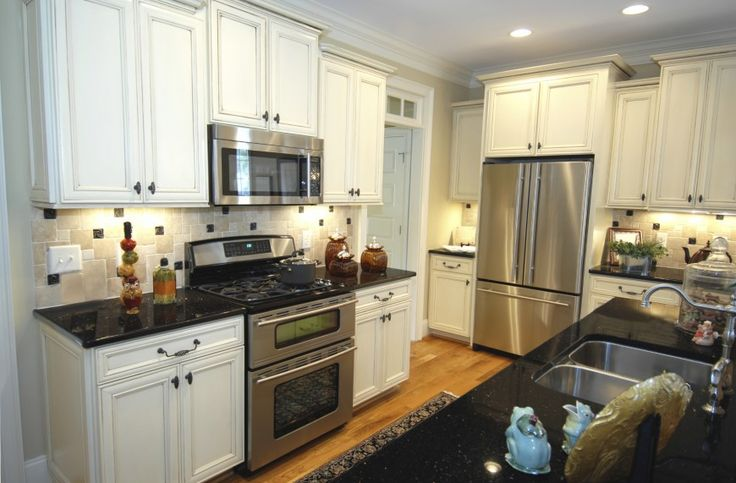 Cozy space filled with white cupboards all around, light tile patterned backsplash and black countertops.