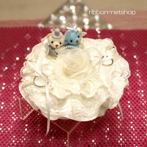 ラウンド型のリングクッションの上にウェディングのクマさんがのったリングピローです。 リボンのところに指輪をかけられます。  挙式が終わった後も飾れるので結婚のお祝い、プレゼントにもおすすめです♪