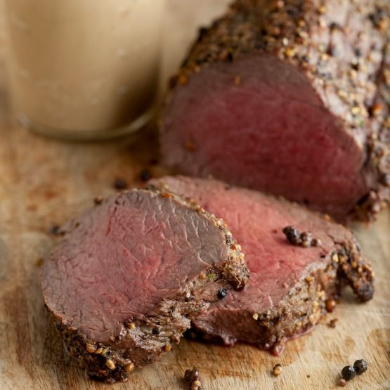 """""""Oven roasting a whole filet of beef is an impressive, easy and delicious way to serve a crowd during the holiday season. The whole beef tenderloin is spread with soft butter, crusted with cracked rainbow peppercorns, and then baked until your desired doneness. A smooth, creamy and savory roasted garlic sauce is the perfect pair for the tenderloin while serving!"""" - Taylor from Taylor Takes a Taste"""