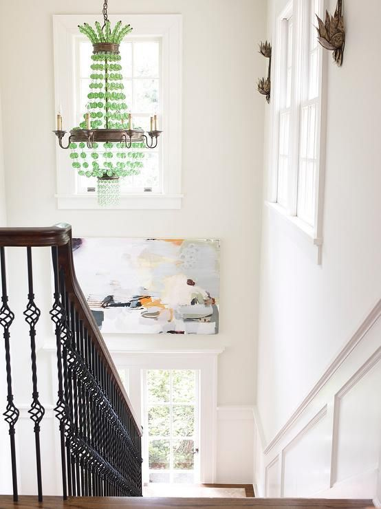 Chic two story foyer is painted Benjamin Moore China White fitted with a wainscoted staircase illuminated by a Currey & Co Green Goddess Chandelier.