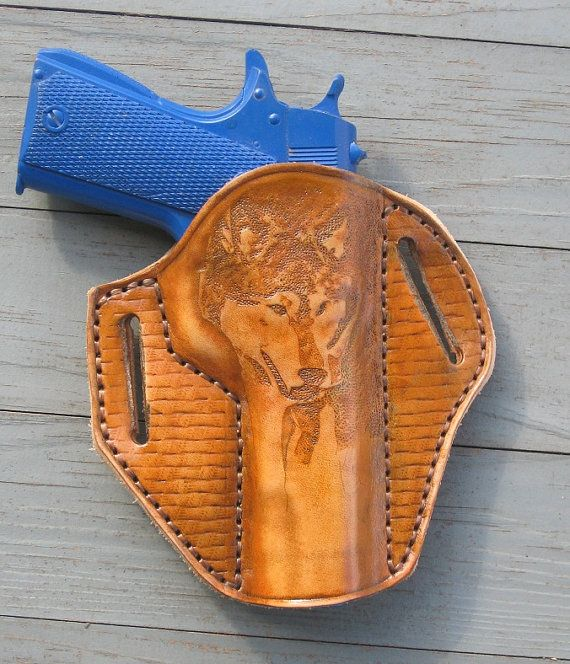 Hand made leather holster, wet formed to the Colt 1911 (will fit most 1911 clones). Hand tooled wolf on the front with basket weave side