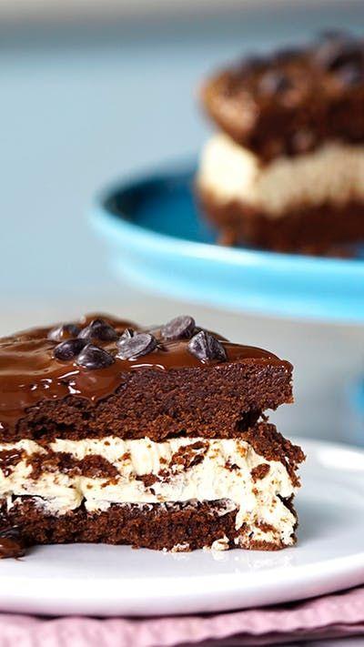 Receita com instruções em vídeo: Já imaginou que incrível a combinação de bolo e brownie? Ingredientes: 500g chocolate meio amargo picado, 200g de manteiga, 1 xícara açúcar, 4 ovos, 2 xícaras farinha de trigo, 200g de manteiga em temperatura ambiente, 200g de açúcar de confeiteiro, 50g de açúcar mascavo, 1 colher de chá de essência de baunilha, ¾ xícara de gotas de chocolate