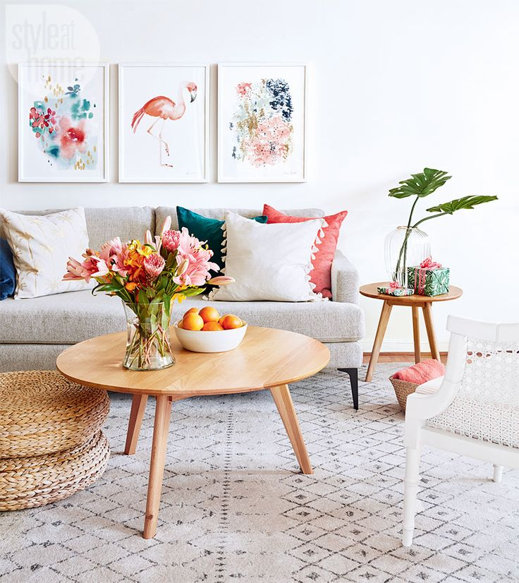Hot-hued blooms, big palm leaves and a bowl of citrus fruits pack a tropical punch in the living area. The neutral sofa and textured pieces like the cane-back sidechair and woven pouffes create a perfect back- drop for any style of holiday decorations. | Image: Stacey Brandford | Designer: Morgan Lindsay | #StyleAtHome #Entertaining #HolidayHome #Christmas