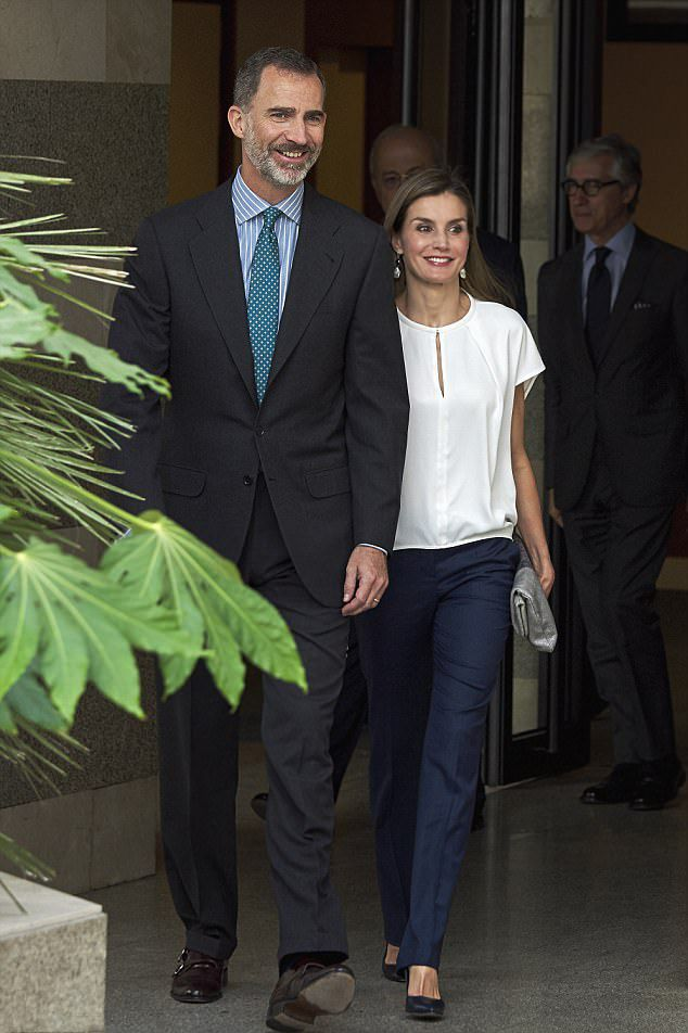 Spanish King Felipe was looking dapper in a dark suit, teamed with a striped shirt, while his wife Spanish Queen Letizia, who showcased her slim figure in navy tailored trousers, teamed with a simple white top with a cut out detail, and added a mettalic silver clutch bag, as they visited the telefonic hotline central for gender violence assistance in Madrid
