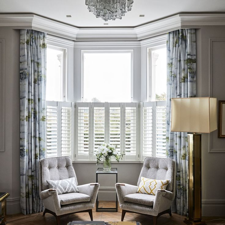 A beautiful bay window, fitted with classic shutters for privacy and a heritage touch, offers the perfect backdrop for a pair of mid-century modern armchairs. Matched with the reflective glass surfaces, these bring a sense of balance to this grown-up living space. 'I admire the power of symmetry,' says the owner, who has used rich textures and a mixture of surfaces to add depth to this scheme. Armchairs Sarah Potter Upholstery Villa Nova Curtains Black Edition