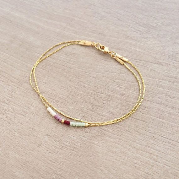 Delicate double-strand bracelet made of a thin chain with a colorful beaded accent. The materials are plated with a thin layer of pure gold 1 micron.
