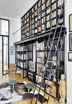 double-height metal bookshelves, bottom unit deeper to provide room for 2nd level walkway, accessed by metal library ladder, by Laureen Rossouw, Cape Town, South Africa