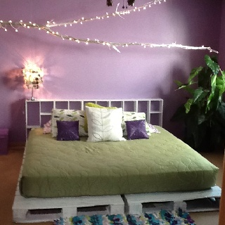 King size platform bed made from discarded pallets. Tree branch spray painted silver with lights.  New bedroom for kids when they come home from camp!