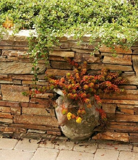 Dry stone wall with integrated pot. Water draining off a slope can seep through the rocks, instead of causing pressure on a cemented wall. westphoria.sunset.com
