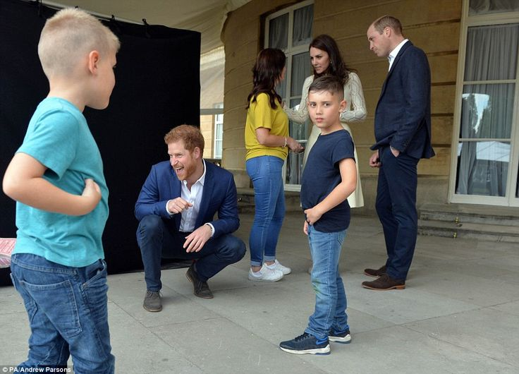 Prince Harry (2nd Left), The Duke and Duchess of Cambridge backstage with Samantha Davidson (centre) and her children Jayden 8, Jamie 6, Amelia, 4, during a tea party at Buckingham Palace