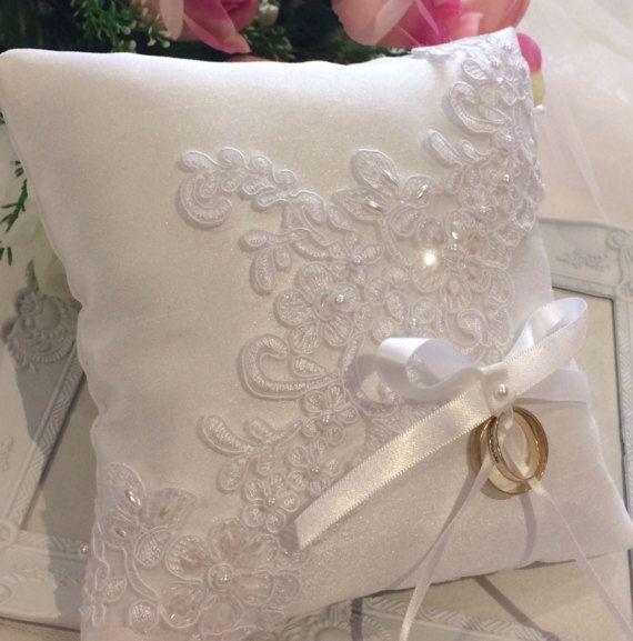 Mano-fatta con amore  Rachael Silk Satin Ring cuscino portatore  Questo elegante e squisito anello portatore cuscino è realizzato in raso di seta bianco e ha una splendida pizzo motivo mano - cucito in diagonale tutta la parte anteriore del cuscino anello. Il pizzo è stato in rilievo con una perle e perle di conteria e deselezionare paillettes. Un fiocco di nastro di raso bianco si trova alla base del merletto con nastri di raso bianchi più stretti per legare gli anelli. La prua è associata…