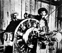 In what is considered the first industrial use of alternating current in 1891, workmen pose with a Westinghouse alternator at the Ames Hydroelectric Generating Plant. This alternator was used as a generator producing 3000 volt, 133 Hertz, single-phase AC.