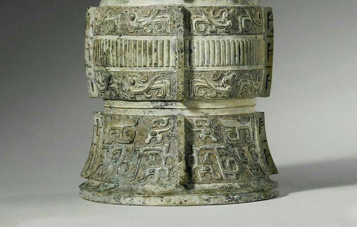 The vessel is cylindrical with four notched flanges down the sides, elegantly cast with 'taotie' masks on the foot in high relief with prominent eyes, ears, forehead shield and hooked horns, flanked by dragons with slim S-shaped bodies and dragon heads, the middle section with a band of vertical ribs between bands of confronted birds with curled crests, beaks and tails, and protruding eyes.