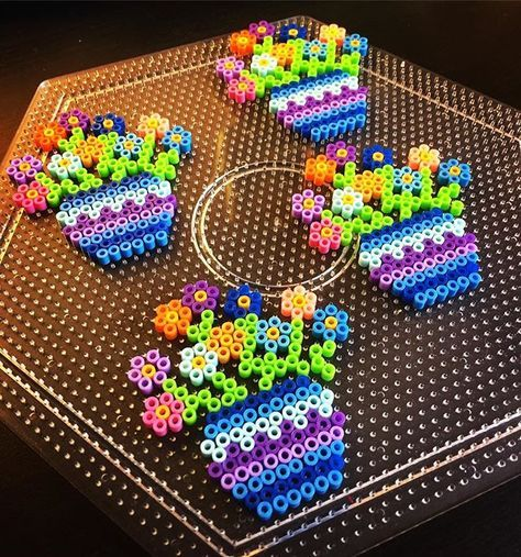 Found this cute pattern on Pinterest to make for my Aunts in Puerto Rico. #flowers #Perler #miniperlerbeads #miniperler