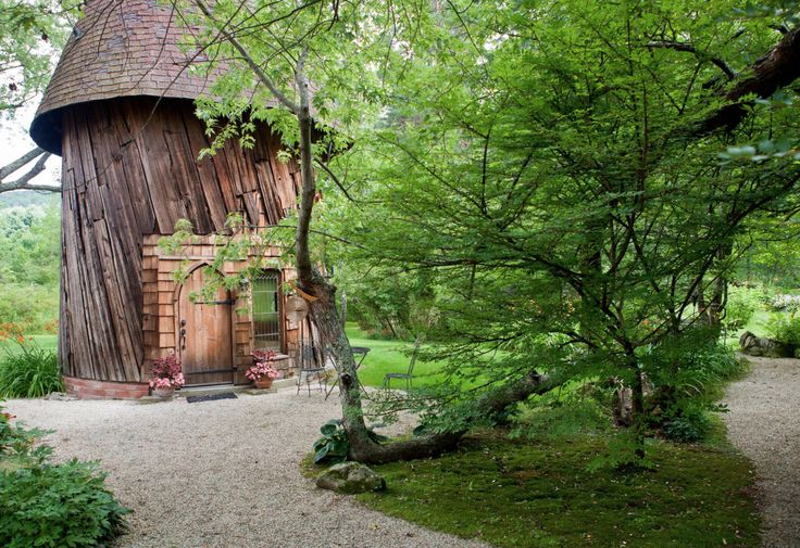 Peer out over the lily pond of a silo studio cottage that looks like the grand trunk of an elder tree.