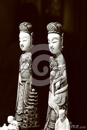 Two ceramic figurines. The first depicts a woman with a bouquet of flowers and a stork. The second depicts a woman with a basket of flowers and a small pagoda