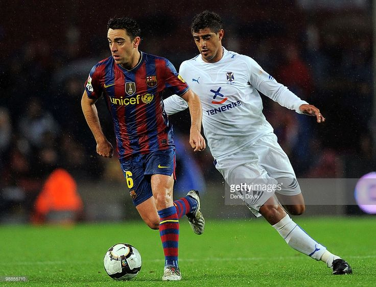 Xavi Hernandez (L) of Barcelona is persued by Roman Martinez of Tenerife during the La Liga match between Barcelona and Tenerife at Camp Nou stadium on May 4, 2010 in Barcelona, Spain.
