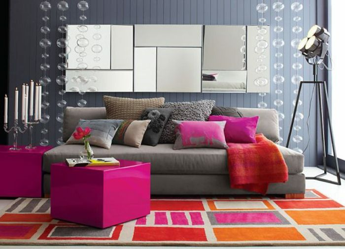 idee deco salon, tapis en rose et orange, tabourets pourpres, mur gris, bougeoirs antiques