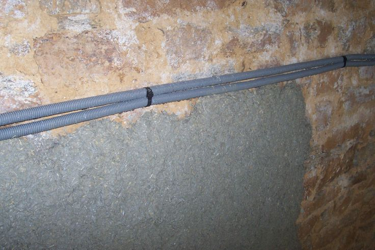 Les gaines électriques sont noyées dans la 1ère couche d'enduit (dégrossi). Elles sont fixées bien tendues avec des chevilles et des colliers plastiques (la chaux attaque le métal)