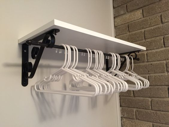 Solution for bedroom without a closet.  Brackets, board and cafe curtain rod from Lowe's created a place to hang clothes and a shelf.: