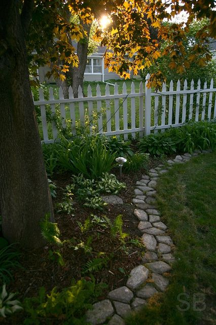 white picket fence and stone border