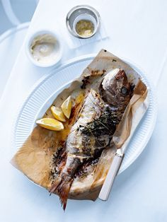 whole baked fish with lemon salt and aioli 1 x 750g whole fish, such as snapper or bream, scaled and gutted+ 100g softened butter 4 cloves garlic, crushed lemon wedges, to serve lemon salt 1 tablespoon finely grated lemon rind 2 tablespoons sea salt flakes aioli ½ cup (150g) whole-egg mayonnaise 2 cloves garlic, crushed Preheat oven to 200°C (390°F).