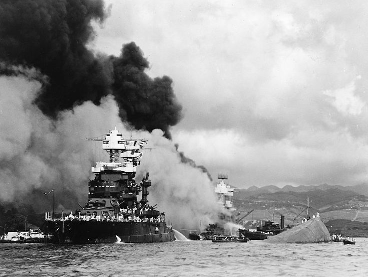 USS Maryland at Pearl Harbor Attack next to overturned USS Oklahoma; USS West Virginia is burning in background.