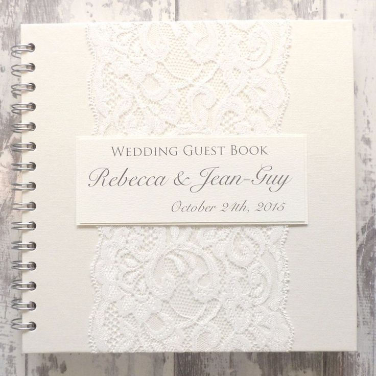"""The DesignThis beautiful wedding guest book oozes elegance and is dressed with delicate ivory vintage lace and personalised off white card panel printed with your details. The Little Details   Wire bound with ivory covers. Thefinest quality ivory cartridge paper pages (150gsm). Measures 20cm x 20cm (8"""" x 8"""") Choose from 35 pages (70 sides) or 70 pages (140 sides). Presented in it's own 100% cotton bag to keep your memories safe. 40 ribbon colours to choose from.   What Happe..."""