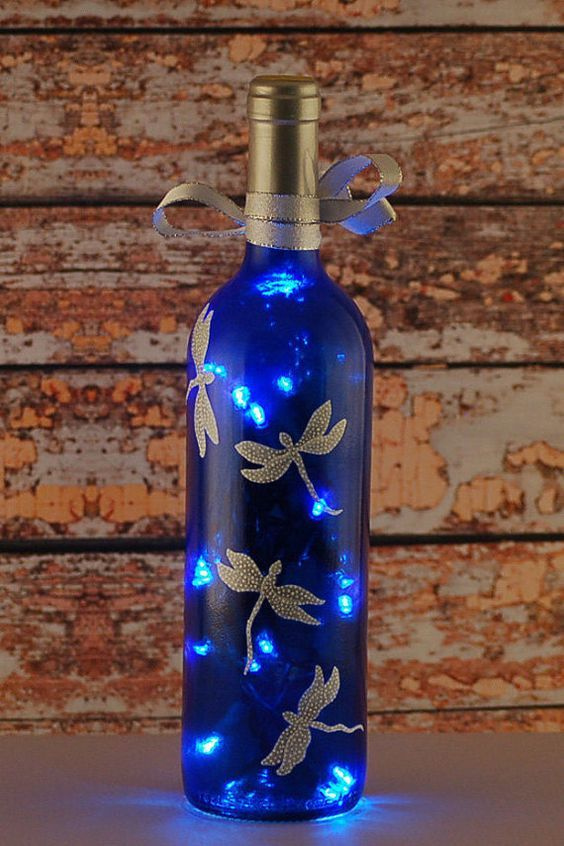 Blue and white dragonfly wine bottle lamp. An empty clear wine bottle was reclaimed and repurposed into this wine bottle light. After cleaning and removing the labels, the clear bottle was tinted a deep blue. Silver and white dragonflies were hand painted onto the blue surface. A hole was drilled near the base of the bottle in the back to allow a plug-in string of LED lights to be inserted into the lamp.