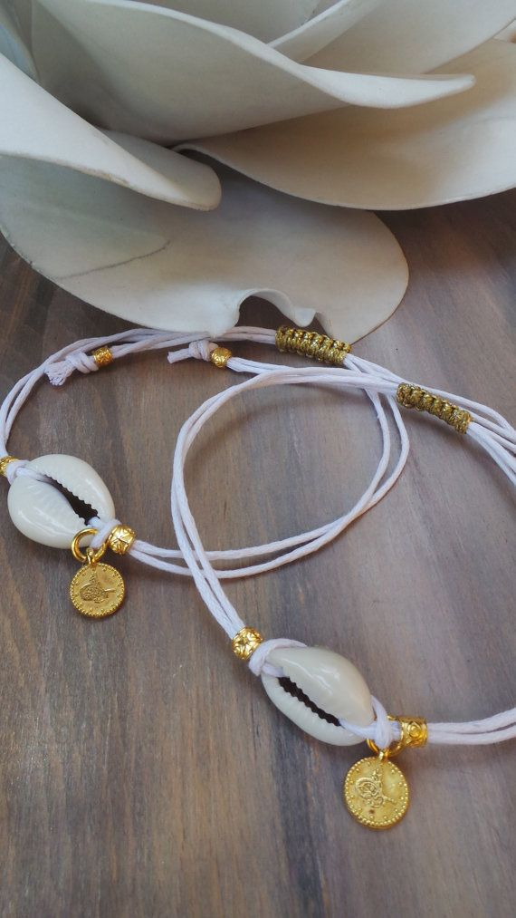 This white and gold bracelet is just perfect for the summer! Wear it on its own or stacked.  To make it I have used a natural cowrie shell and combined it with ornate little gold tubes and a tiny 22K gold plated turkish coin. The white cotton cord is adjustable thanks to the macrame knot. To adjust it just pull the cord ends at either simultaneously.  If you find the cords to long you can tie the knots higher and snip off the ends. Options: You can choose whether you prefer a larger or small…