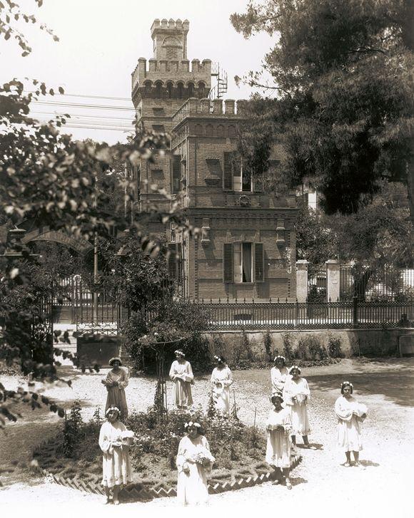 Ο Πύργος της Ευτυχίας από τον κήπο της οικίας Χασά Ασίζ Καπαντζή την εποχή που στέγαζε τα εκπαιδευτήρια Αγλαϊάς Σχινά (περιοχή Ανάληψη)
