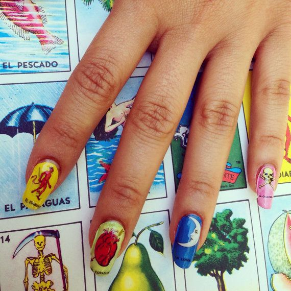 Get these hella cute and creative Cha Cha Covers Nail Decals in various designs.  They are water slide decals which peel easily from paper once cut and dipped in water, they adhere easily over a fresh topcoat and can last for a week if preserved well under a topcoat. Fast, Fun, Easy Steps-- INSTRUCTIONS INCLUDED!1) Loteria2) Phases of the Moon3) Dodgers4) Red Virgen de Guadalupe5) Virgen de Guadalupe6) Sarape (not pictured)