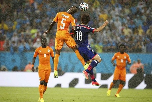 Japan's Yuya Osako fights for the ball with Ivory Coast's Didier Zokora.