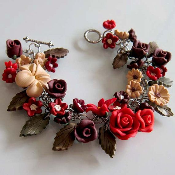 Lush and sensual, this polymer clay luxury charm bracelet features a host of sculpted petals and velvety blooms. Lilies, roses, and other flowers