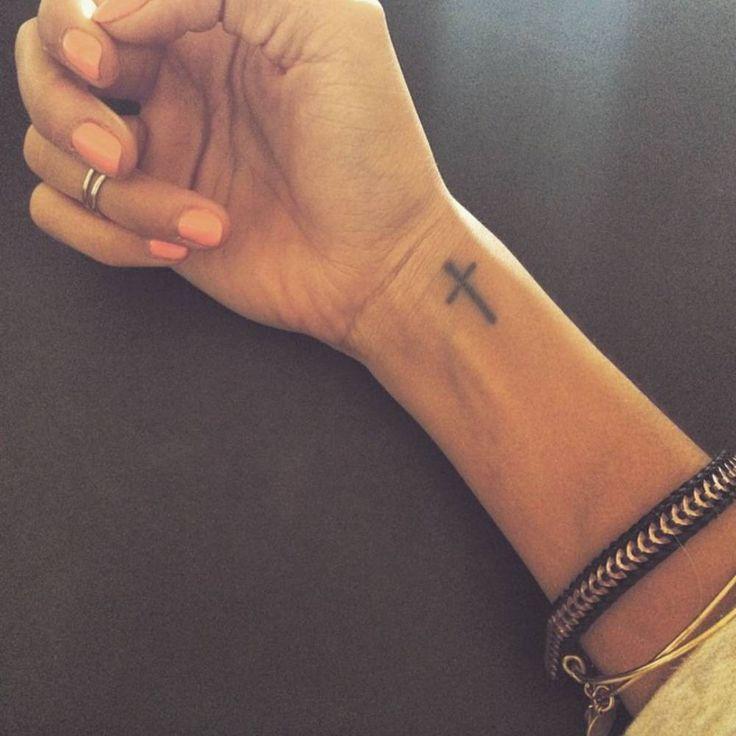 Tatuaje de una pequeña cruz cristiana en la muñeca de Tenika.
