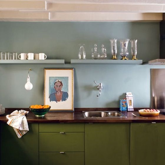 A kitchen in Paris by architect Phillippe Harden, a portrait propped on the wood counter picks up the color scheme of pale blue and olive green.