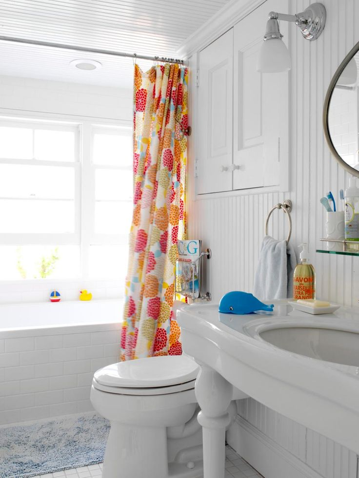 """When designer Tara Seawright's clients bought an outdated waterside cottage, they turned to her for help modernizing the space on a tight budget. """"By painting the floors a bright white and using strategic pops of color — like a colorful shower curtain — against a neutral background, we gave the home a more current look,"""" says the designer."""