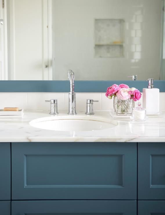 A gorgeous peacock blue bath vanity is fitted with a marble countertop holding a round sink beneath a polished nickel faucet mounted beneath a peacock blue framed mirror.