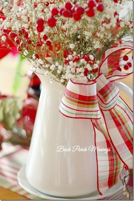 pitcher of red and white flowers