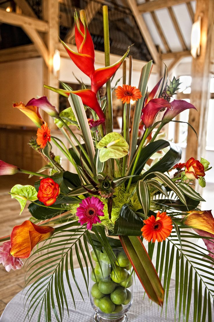Tropical pedestal arrangement of bright flowers to greet guests at Rivervale Barn by www.tarniawilliams.co.uk