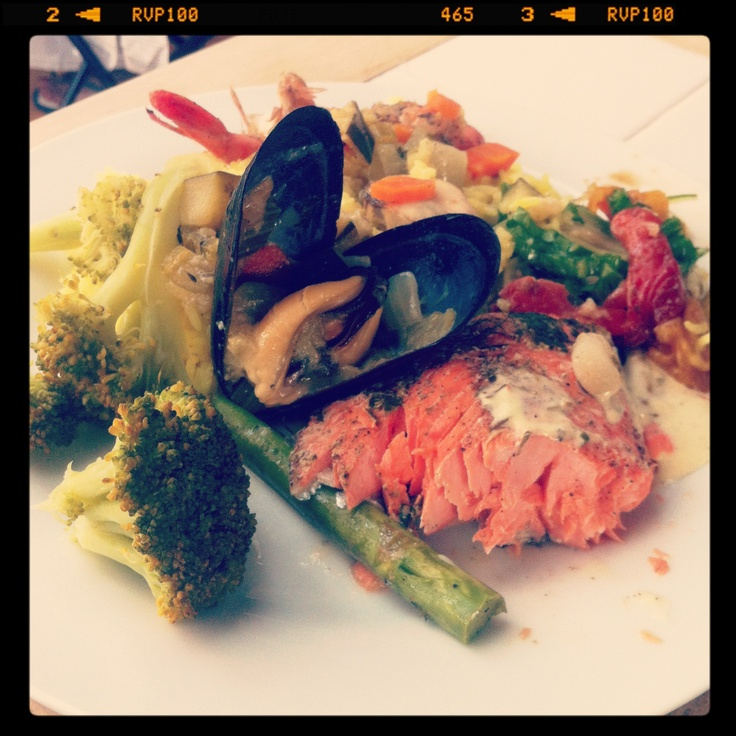 salmon and mussels in white wine sauce with saffron rice and veggies.