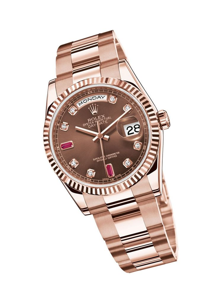 rolex oyster perpetual in rose gold w chocolate brown face & ruby accents.